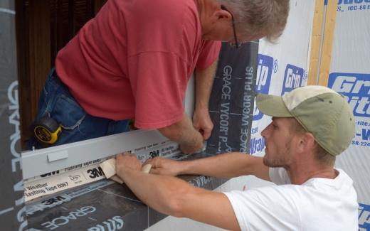 Michael and Matt sealing window frame