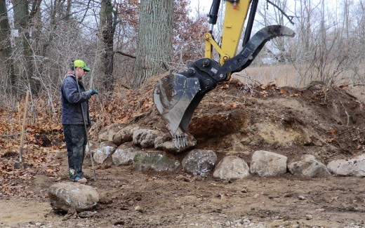 Bruce from Bostwick Excavating guiding stone placement